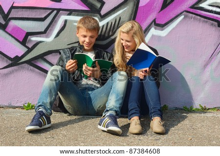 teenage couple studying in the park