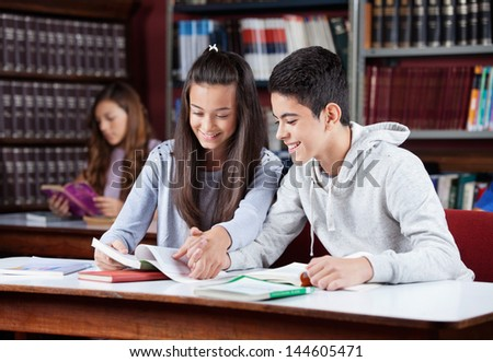 Teenage couple studying together while holding hands at table in library - stock photo