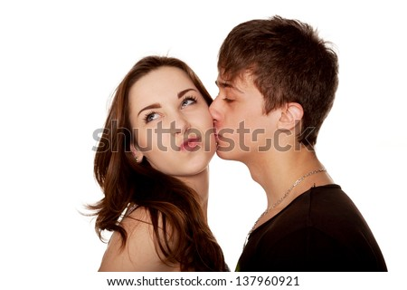 Teenage couple. The boy kissing girl. A girl makes a face, grimacing. Isolated on white background