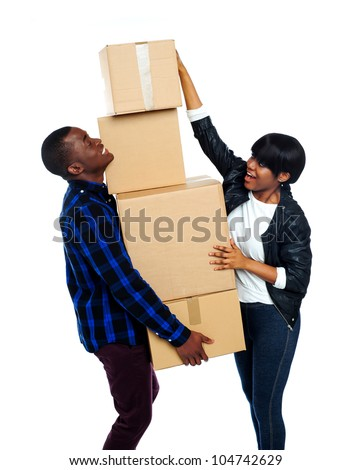 Teenage couple with cardboard boxes. Girl trying to make stack high