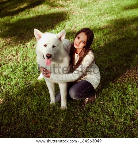 Teenage cute girl with her dog in the park  - stock photo