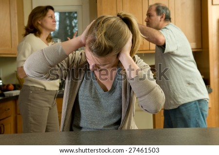 Teenage daughter covers ears during family argument - stock photo