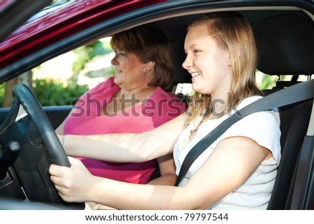 Teenage daughter gets a driving lesson from her mother or an instructor. - stock photo