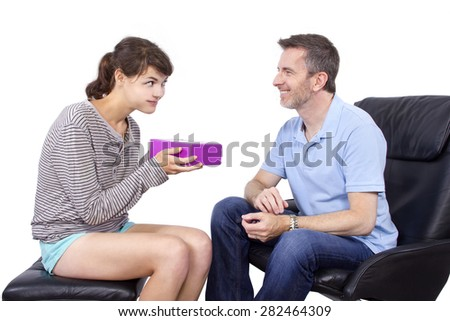Teenage daughter giving a surprise gift to her single father.  They are isolated on a white background.  The image depicts Father's Day - stock photo