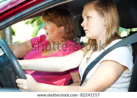 Teenage driver and her mother about to have a car accident. - stock photo