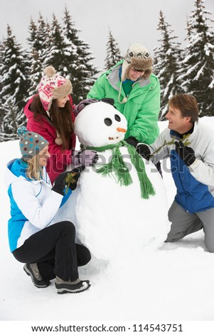 Teenage Family Building Snowman On Ski Holiday In Mountains - stock photo