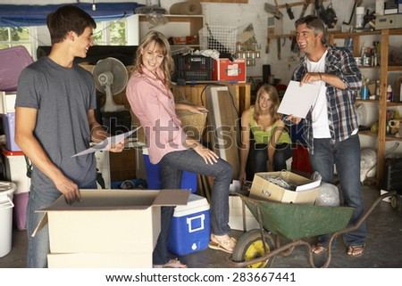 Teenage Family Clearing Garage For Yard Sale - stock photo