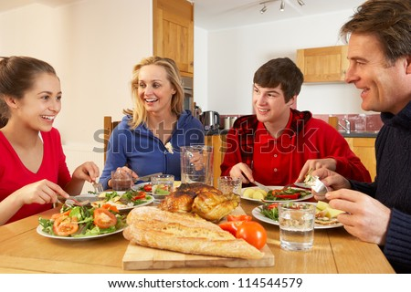 Teenage Family Eating Lunch Together In Kitchen - stock photo