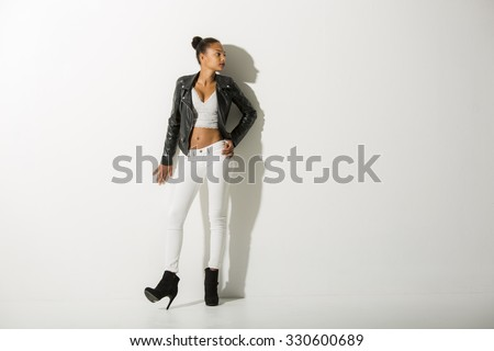 Teenage fashion model leaning towards a white wall looking at camera right.