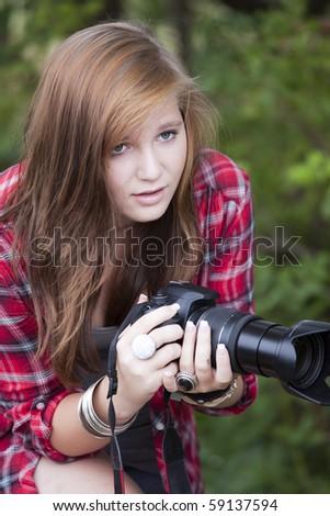 Teenage fasion model holding a camera looking forward - stock photo