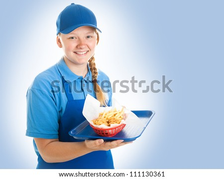 Teenage fast food worker holding a tray of chicken nuggets and fries. Blue background - stock photo
