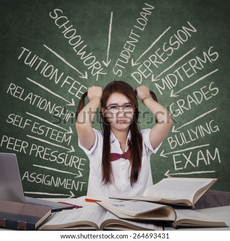 Teenage female student facing many problems and grabbing her hair ties in the class - stock photo