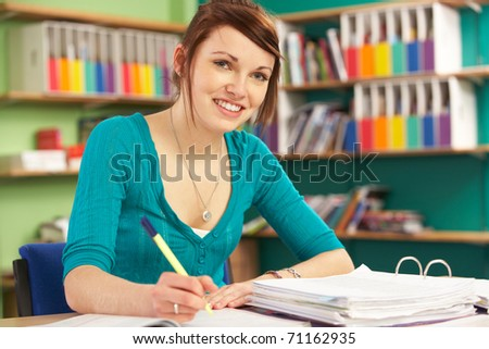 Teenage Female Student In Working In Classroom - stock photo