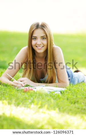 Teenage female student reading on Campus Lawn
