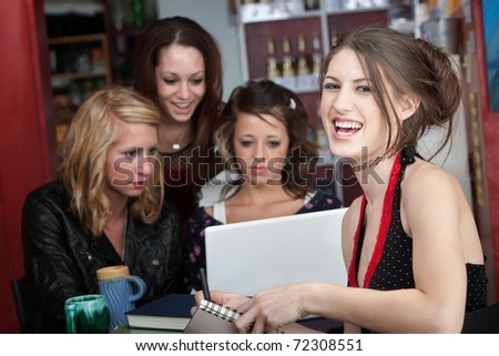 Teenage friends having a good time while studying together in a coffeehouse