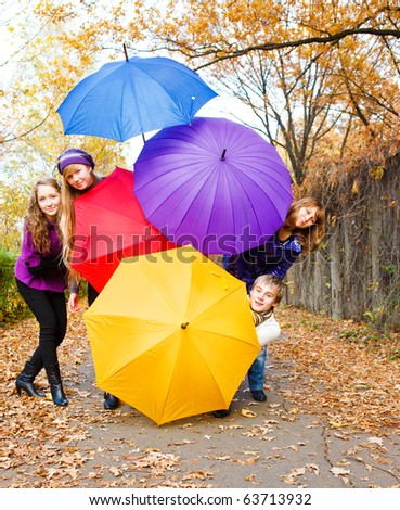 Teenage friends hiding behind umbrellas - stock photo