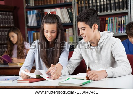 Teenage friends studying together while holding hands at desk in library - stock photo
