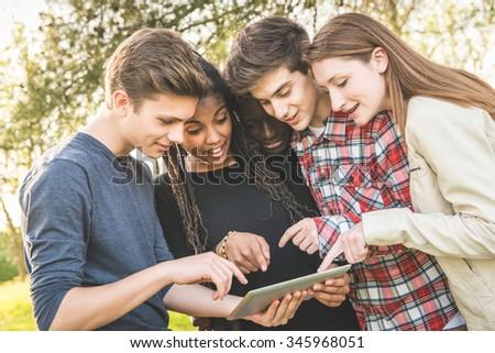 Teenage Friends using Digital Tablet at Park - stock photo