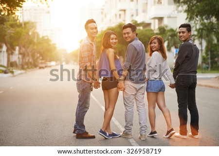 Teenage friends walking together in the street - stock photo