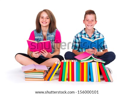 Teenage friends with many books in front on them smiling and reading