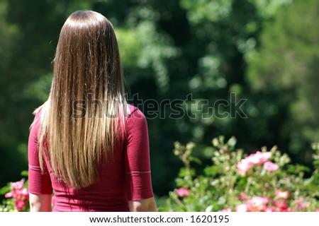 Teenage Girl Admiring Garden - stock photo