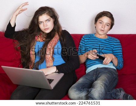 teenage girl and a boy looking annoyed with laptop and phone - stock photo