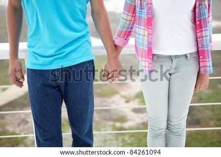 Teenage girl and boy holding hands - stock photo