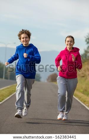 Teenage girl and boy running, jumping outdoor  - stock photo