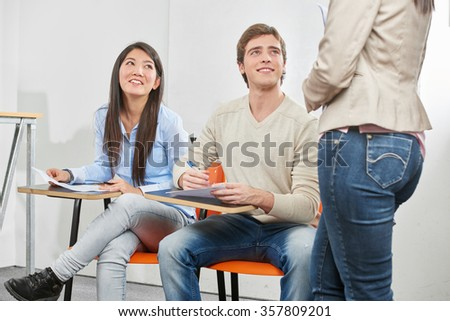 Teenage girl and boy taking a test in their high school classroom - stock photo