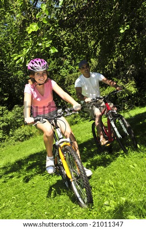 Teenage girl and her father riding bicycles in summer park - stock photo