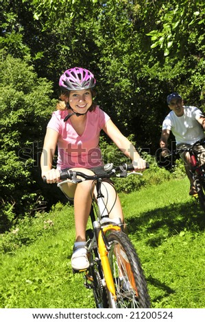 Teenage girl and her father riding bicycles in summer park