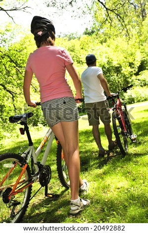 Teenage girl and her father with bicycles in summer park - stock photo