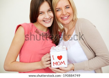 Teenage girl and her mom with giftbox looking at camera and smiling - stock photo