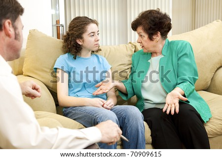 Teenage girl and her mother meeting in a family therapist's office for counseling. - stock photo