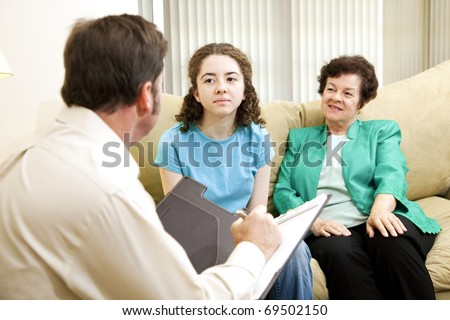 Teenage girl and her mother meeting with a psychologist.  Could be some other type of interview. - stock photo