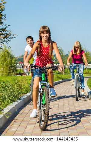 Teenage girl and her parents cycling in a park - stock photo
