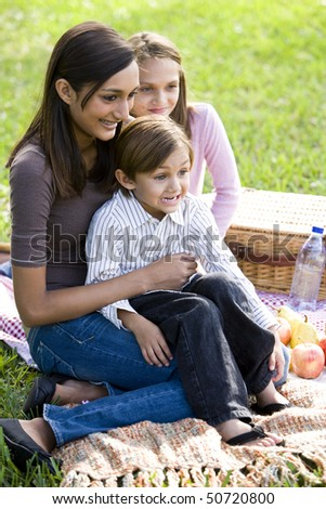 Teenage girl and two younger siblings enjoying picnic - stock photo
