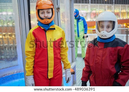Teenage girl and woman dressed in colourful suits and helmets stand near air-tube outdoor.