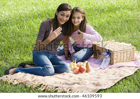 Teenage girl and younger sister enjoying  picnic in the park - stock photo