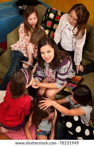 Teenage girl applies facepaint to friends at a sleepover - stock photo