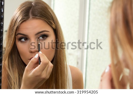 Teenage girl applying eyeliner on eyes - stock photo