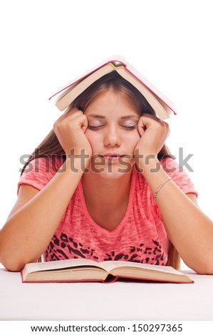 Teenage girl asleep with book on the head over book on the table, on the white background  - stock photo