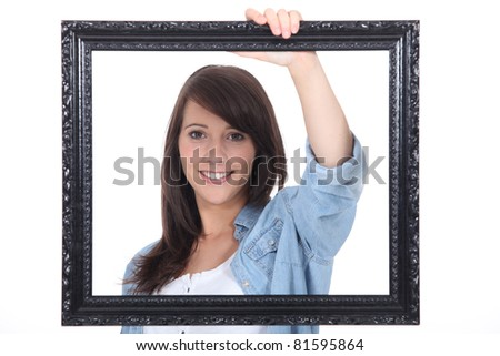 teenage girl behind a painting frame - stock photo