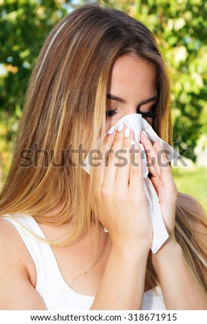 Teenage girl blowing nose outdoors - stock photo
