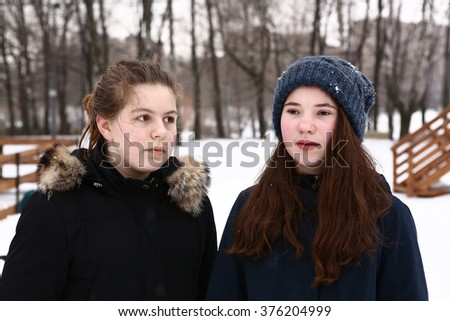 teenage girl close up portrait in fur coat collar and knitted woolen hat on the snowy winter park background - stock photo
