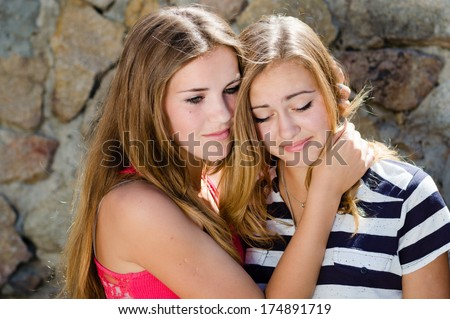 Teenage girl comforting crying friend with warm hug on stone rock wall background - stock photo