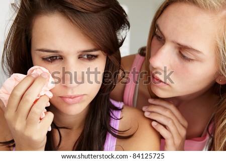 Teenage girl comforting tearful friend - stock photo