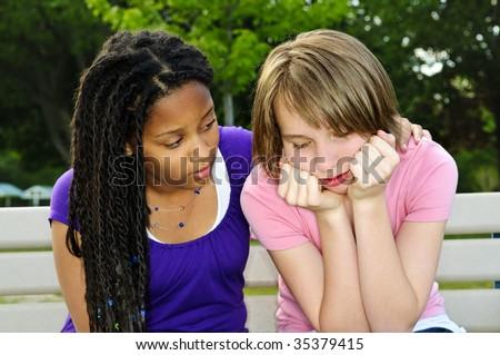 Teenage girl consoling her sad upset friend - stock photo