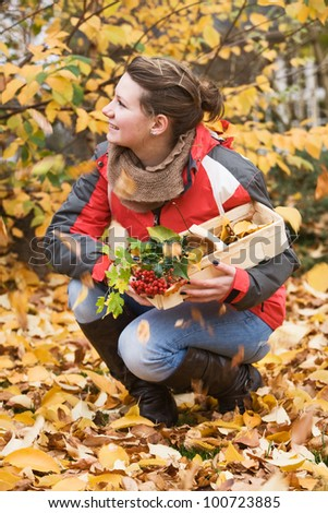 Teenage girl crouching outdoors among falling leaves, autumn - stock photo