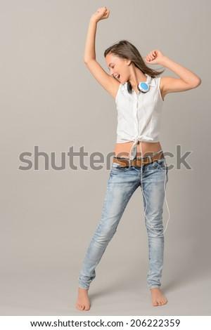 Teenage girl dancing singing enjoy music full length on gray background - stock photo